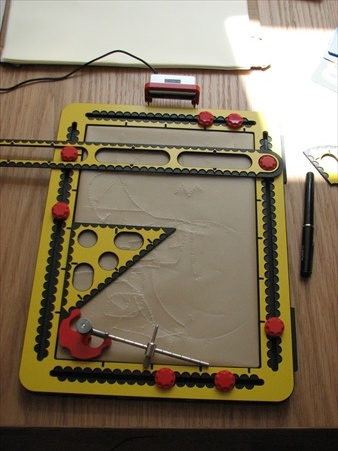 Plastic drawing board with silicon pad and measuring instruments.