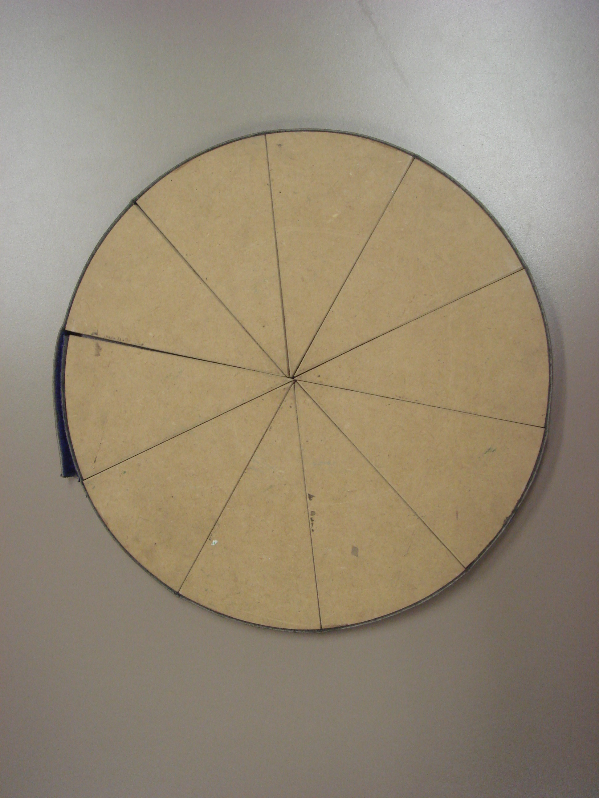 Home-made wooden disc, divided into ten equal pieces.