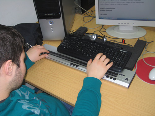 This pupil is using a desktop computer with 80-character braille display